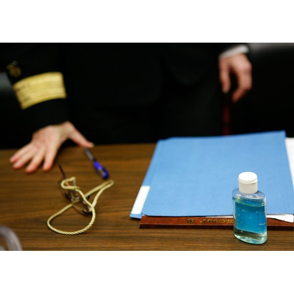A bottle of Purell sits on a desk with a folder and a woman's hand resting on the desk.
