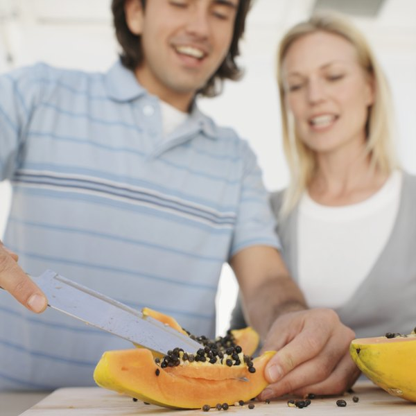 young modern couple slicing fruit in kitchen