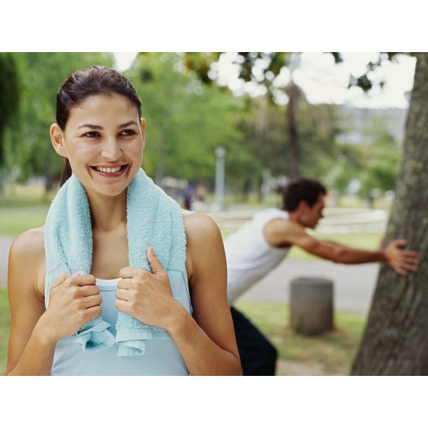 A woman smiling in the park after a work-out with her boyfriend.