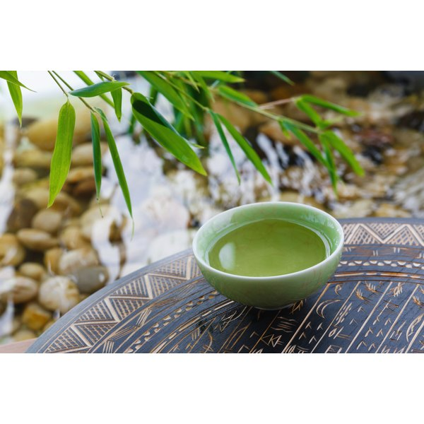 A cup of green tea on a tray near a stream.