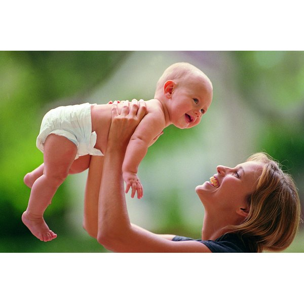 A woman is holding her baby in the air.