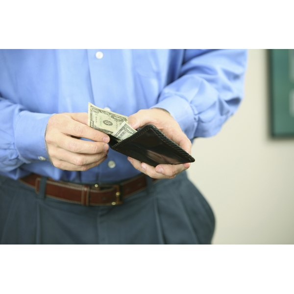 Close-up of a man counting the dollars in his wallet.