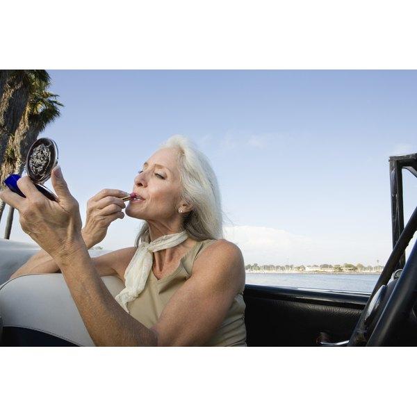A woman applies lip balm to her upper lip.