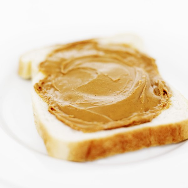Close up of peanut butter on a slice of white bread.
