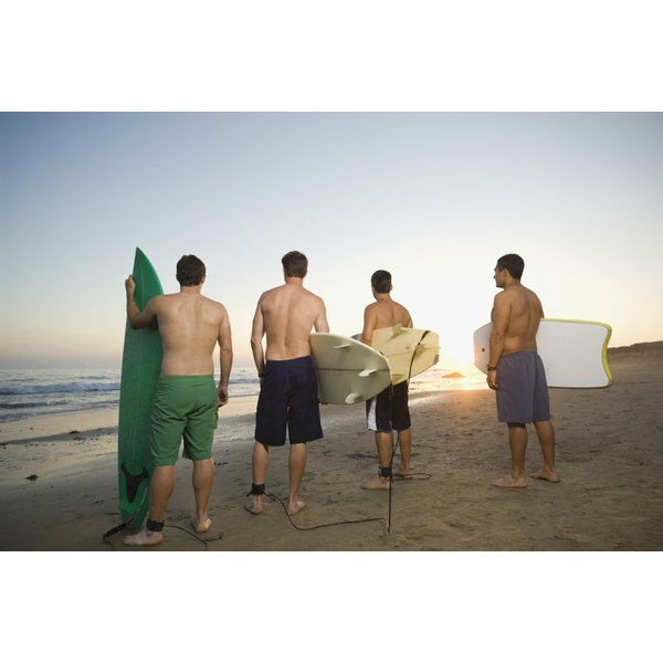 Rear view of young surfer men.