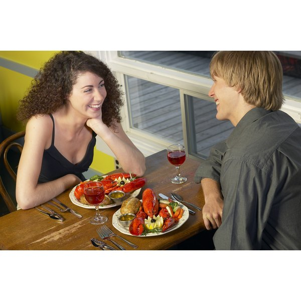 A young couple enjoy sitting down to a shellfish meal including lobster.