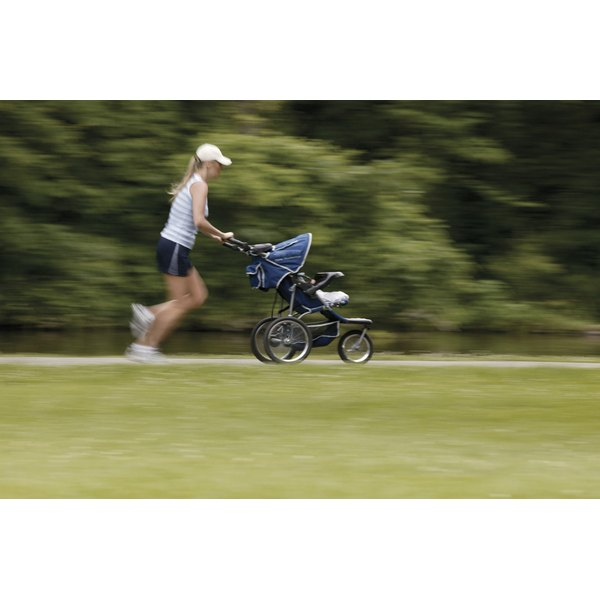 A woman is jogging with a baby stroller.
