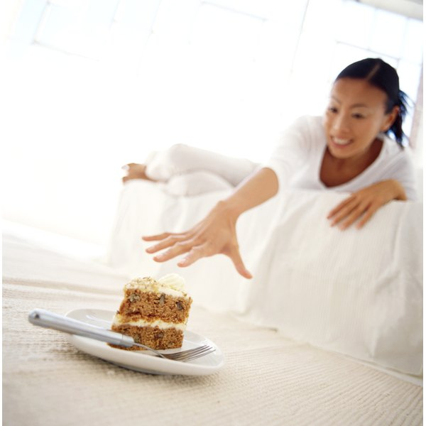 A woman laying on a couch in a white room reaches for a big slice of cake sitting on the coffee table.