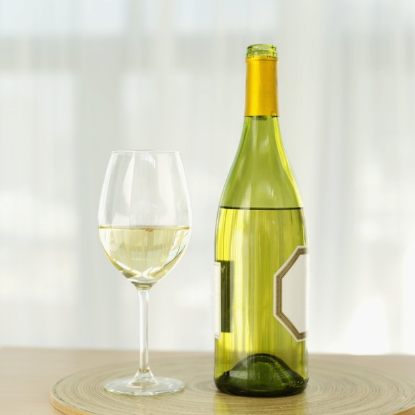 A glass of riesling sitting next to a wine bottle.