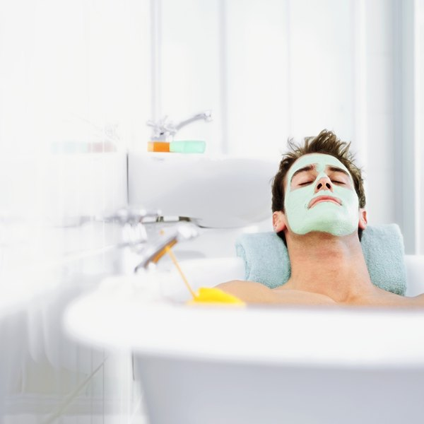 A young man wearing a facial mask in the bathtub.