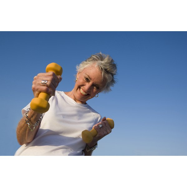 Older woman smiling and holding hand weights.