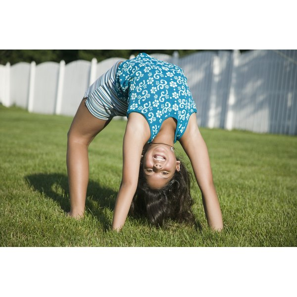 Child doing a backbend in grass in her backyard.