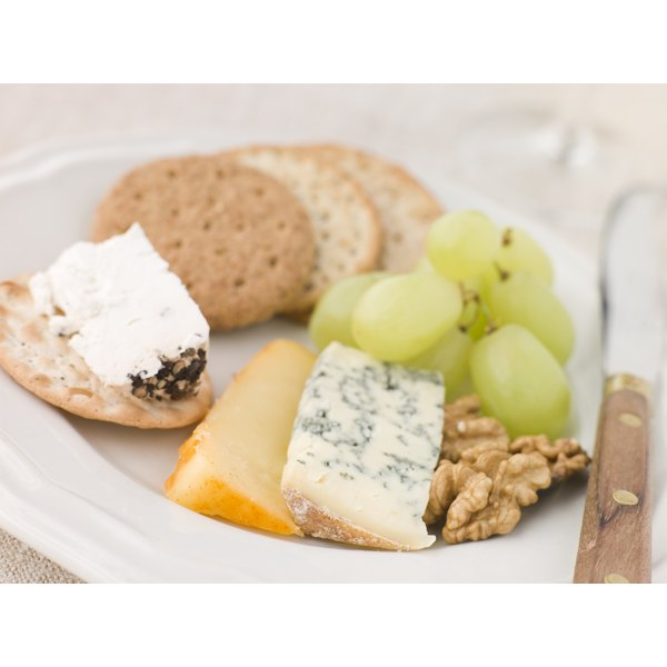 A snack of cheese, crackers, nuts and grapes.