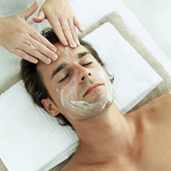 man receiving cream treatment on face