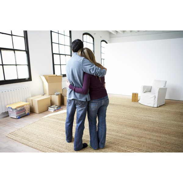 A couple embracing in their new apartment.