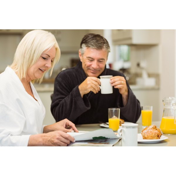 A middle aged couple enjoy orange juice with their breakfast.