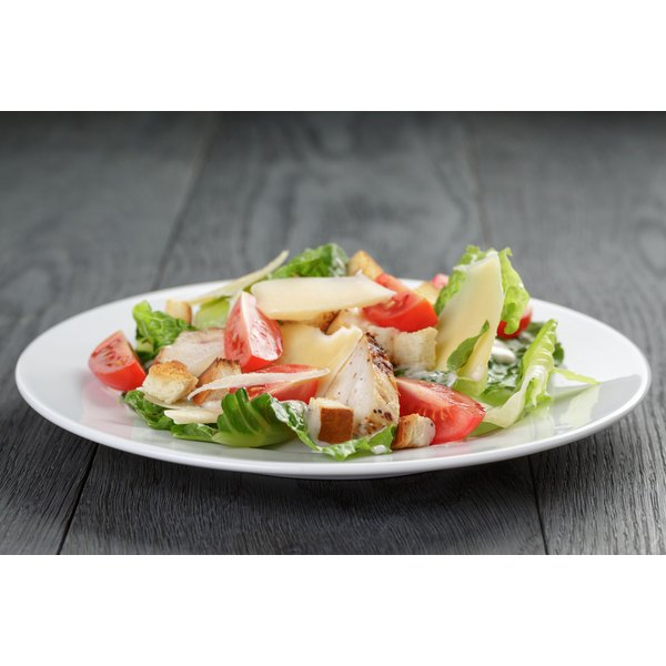 A chicken and tomato salad on a plate.
