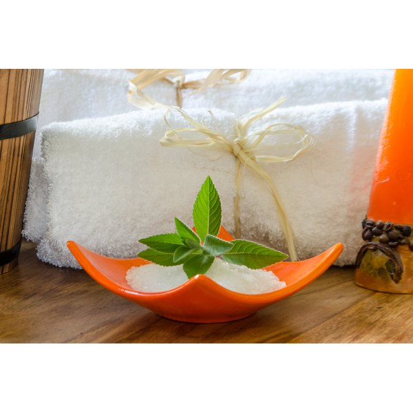Peppermint bath salts in a bowl, a candle and bath towels on a wood table.
