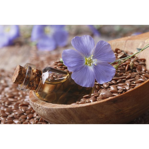 A bottle of flaxseed oil in a wooden spoon with flaxseeds and a blossom.