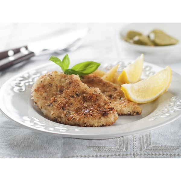 Two chicken cutlets on a plate with lemon and herb garnish.