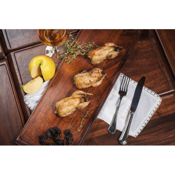 Three cooked quail on a wood serving tray.