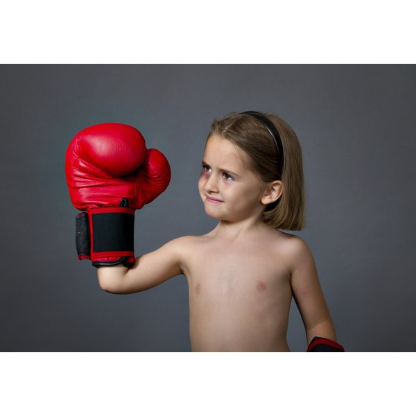 A young girl wearing a boxing glove holds up her fist.