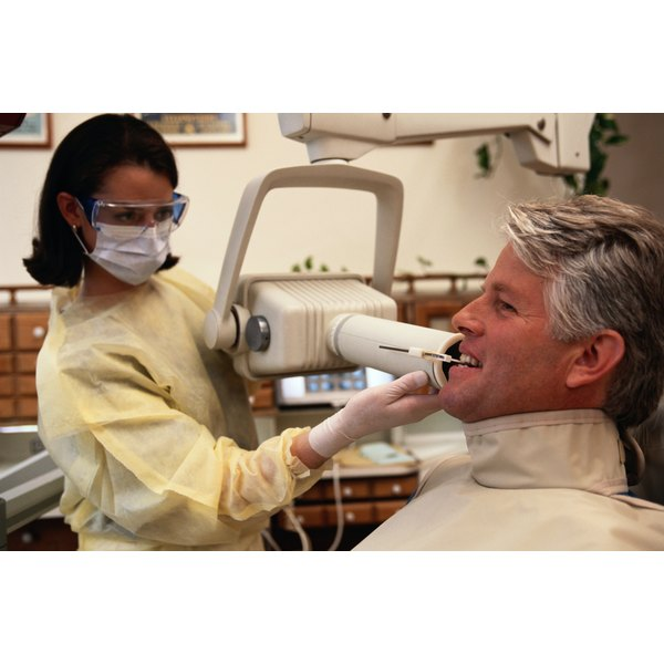 A doctor is giving a patient a dental xray.