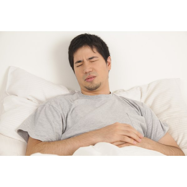 Man in bed holding his stomach
