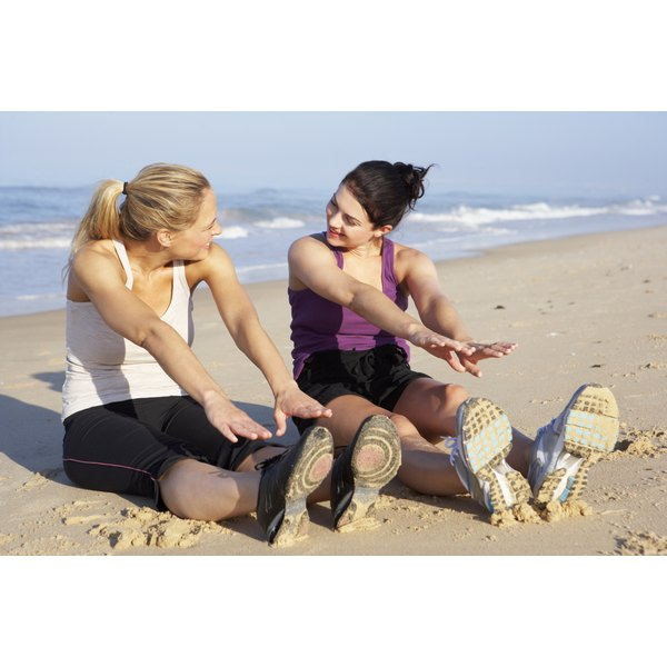 Two fit woman are stretching on the beach.