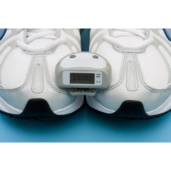 A pedometer on top of someone's tennis shoes.