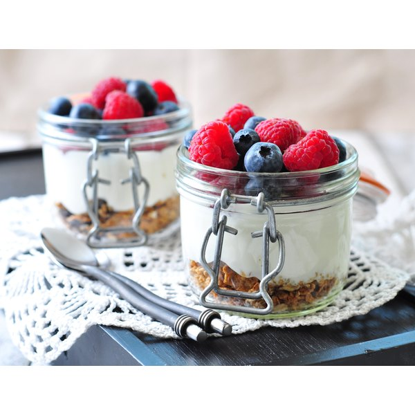 Two yogurt parfaits with granola and fresh berries on a wooden table.
