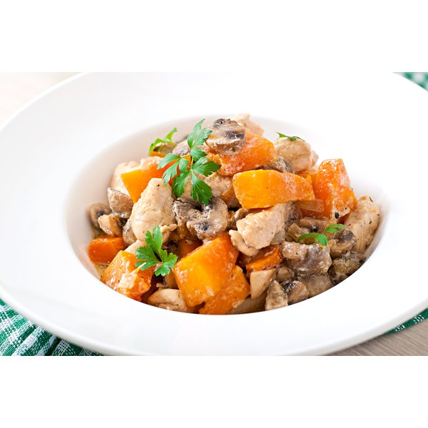 A white bowl of chicken and carrots.