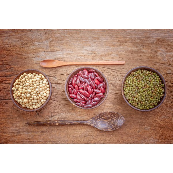 Three bowls of beans on a wood surface.
