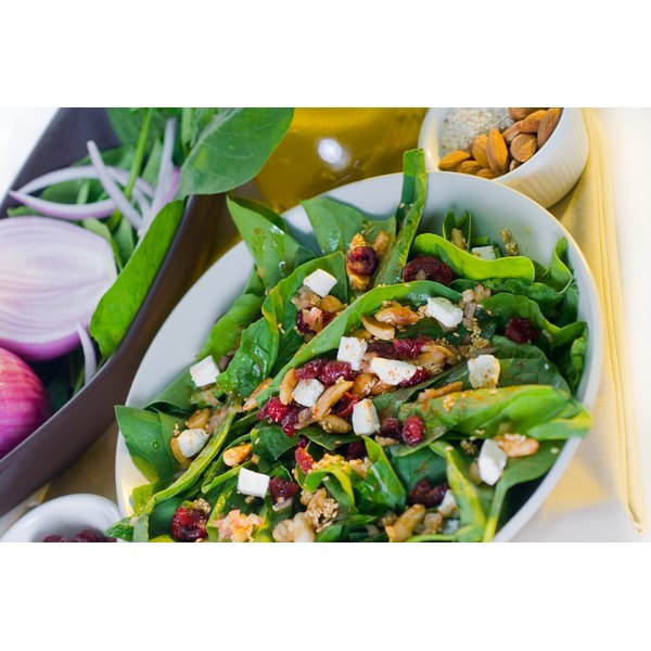 Cranberries sprinkled over a warm spinach salad with almonds, sesame seeds, garlic and cheese.