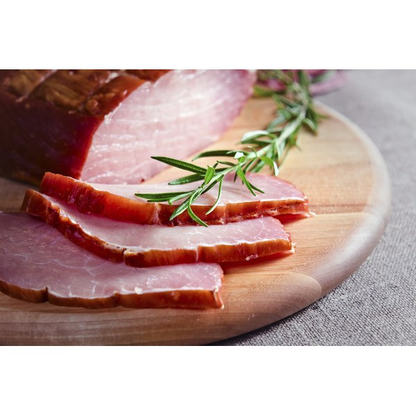 A sliced smoked ham on a cutting board.