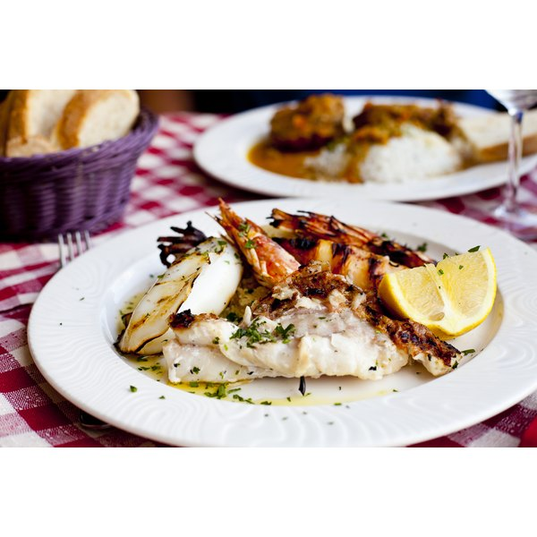 Fish and shellfish on a plate with herbs and lemon.