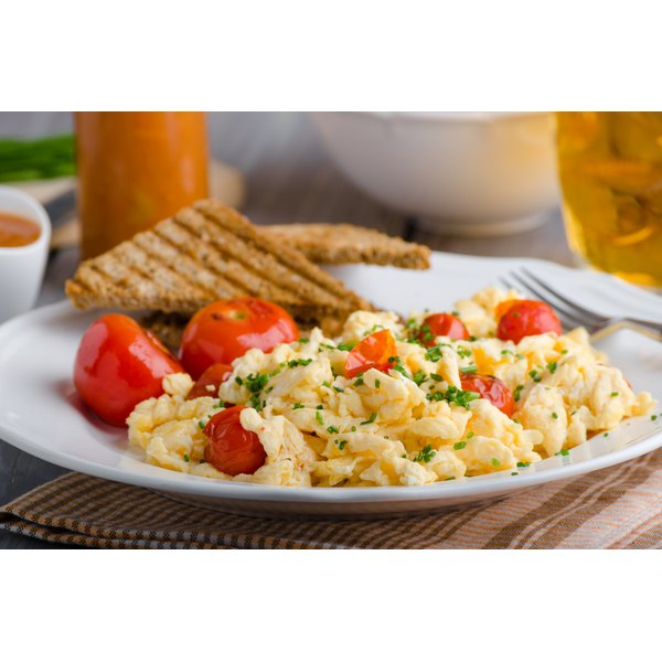 Plate of scrambled eggs with tomatoes