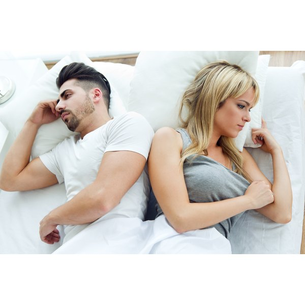 A frustrated man and woman are lying in bed.