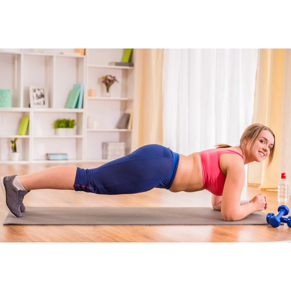 An overweight woman is doing planks.