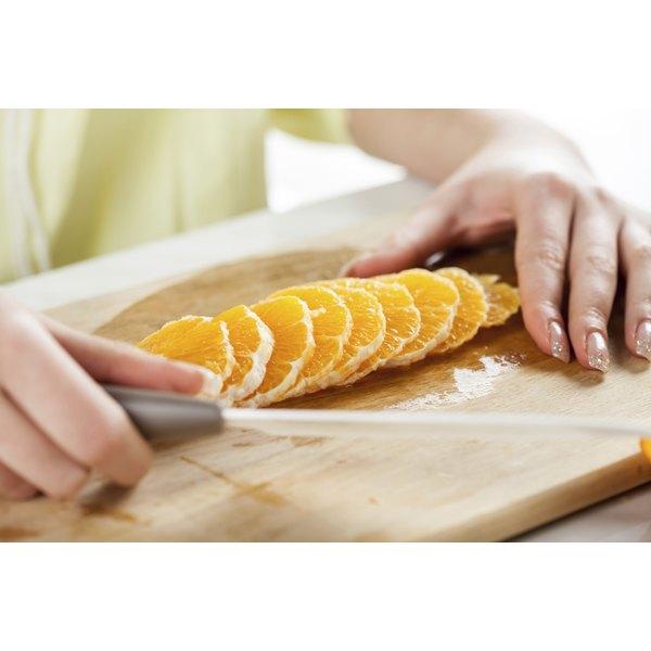 Slicing oranges on cutting board.
