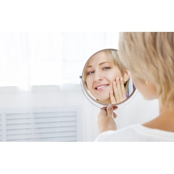 A woman is looking at her skin in the mirror.