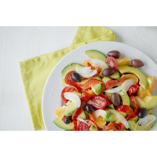 A fresh avocado salad with tomato, red peppers, black olives, onions and oranges.