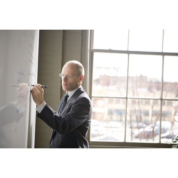 A businessman writing on a white board in a conference room.
