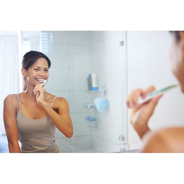 woman brushing teeth in bathroom