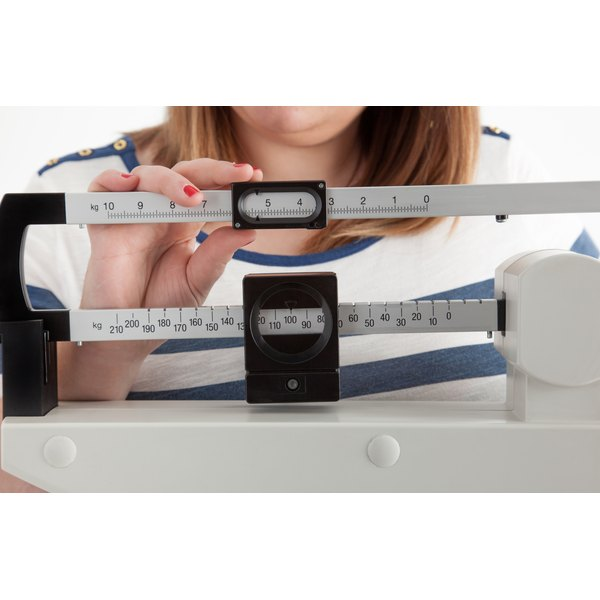 A woman is adjusting a scale.