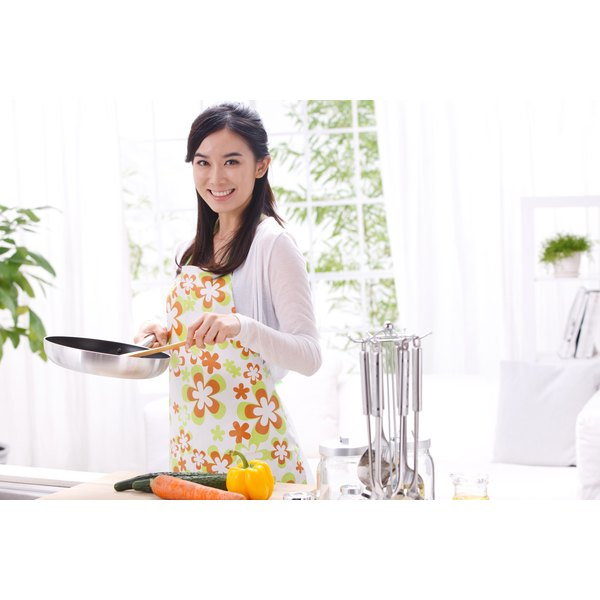 A woman is cooking in the kitchen.