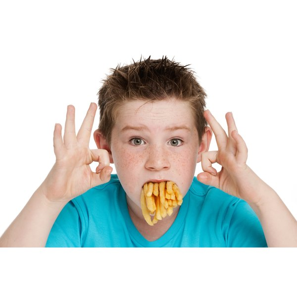 Boy with mouth full of french fries.