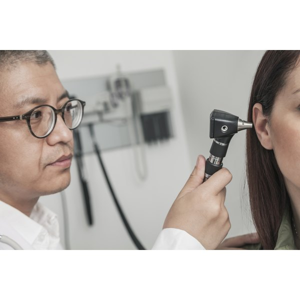 Doctor examining a woman's ear.