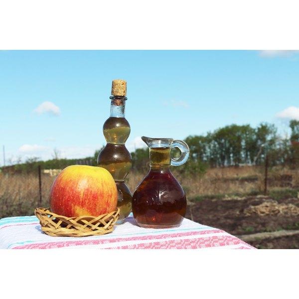 Two bottles of apple cider vinegar.