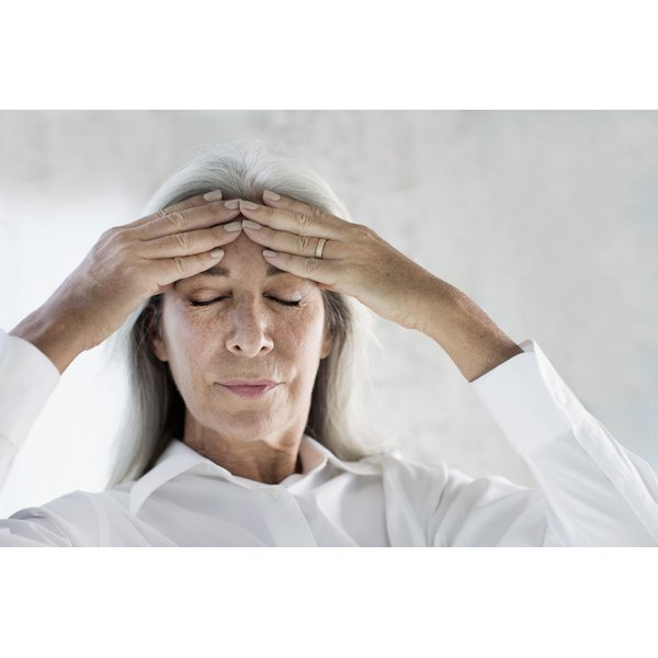 A woman with a headache rubbing her temples.